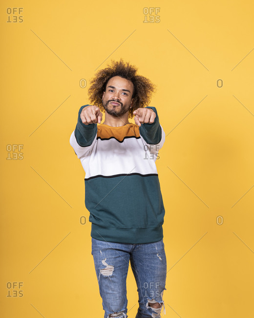 Handsome young man with curly hair pointing while standing against yellow background
