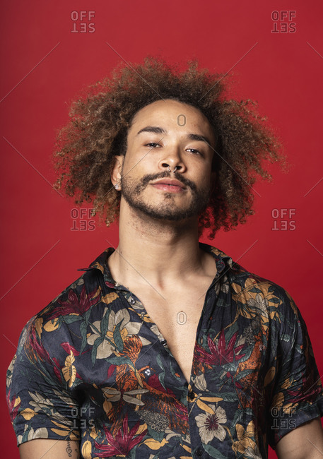 Handsome young man with curly hair standing against red background