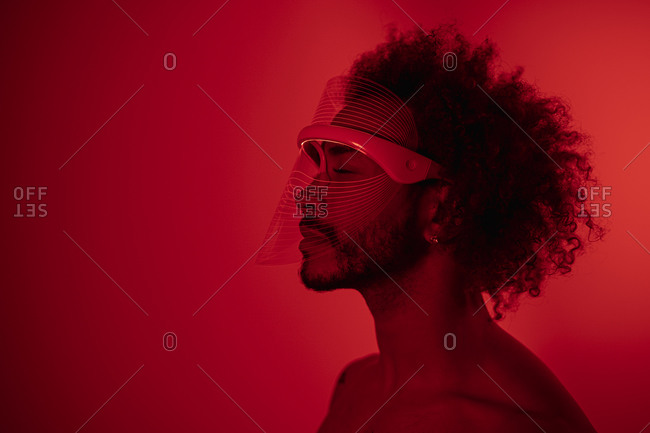 Young man with eyes closed wearing red led light mask against wall at home