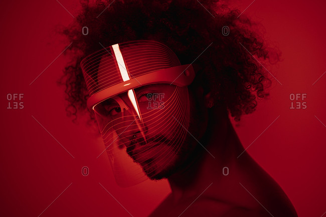 Close-up of young man wearing red led light mask against wall at home