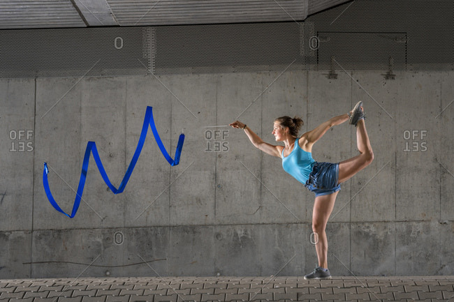 Young woman spinning ribbon standing on one leg against concrete wall under bridge