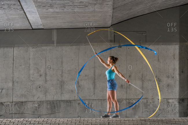 Young woman spinning ribbons while practicing rhythmic gymnastics against concrete wall