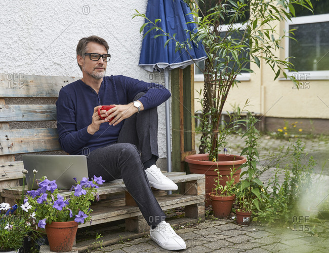 Thoughtful mature man holding coffee mug while sitting on wooden bench at yard