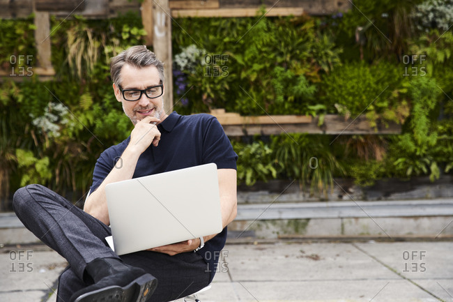 Mature man using laptop while sitting on chair at yard