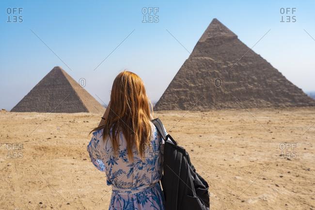 Egypt- Giza Governorate- Giza- Female tourist photographing Giza Pyramids