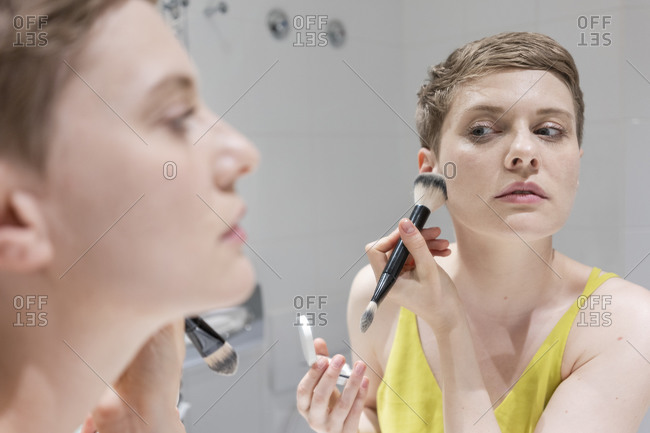 Short haired woman applying make-up with brush while looking at her reflection on mirror in bathroom