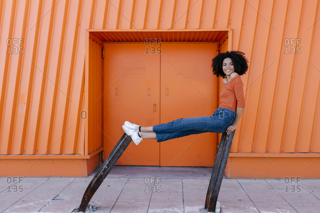 Smiling young afro woman sitting on damaged metal against orange door