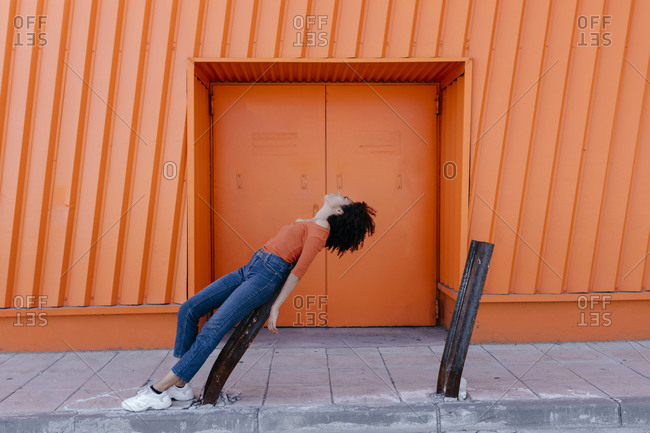Young woman leaning on damaged metal by orange door
