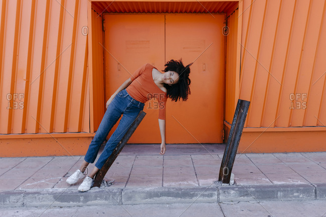 Young woman with afro hairstyle leaning on damaged metal against orange door