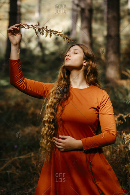 Beautiful woman with eyes closed holding leaves while standing in woodland