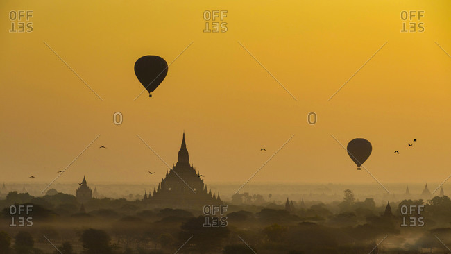Myanmar- Mandalay Region- Bagan- Silhouettes of hot air balloons flying over ancient temples at foggy dawn