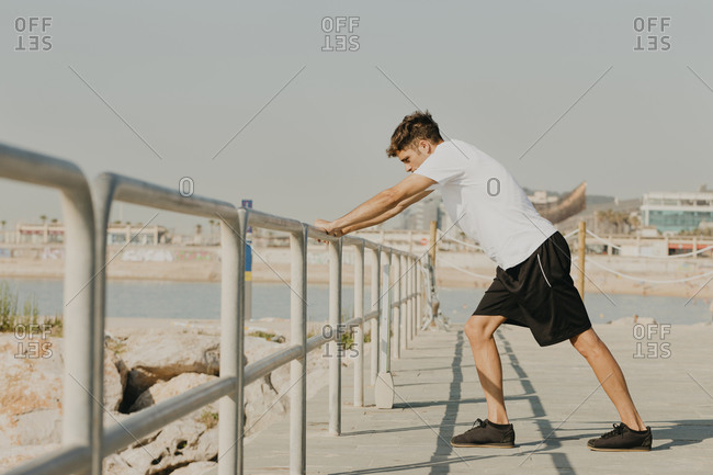 Male athlete exercising while standing by railing at harbor against clear sky on sunny day