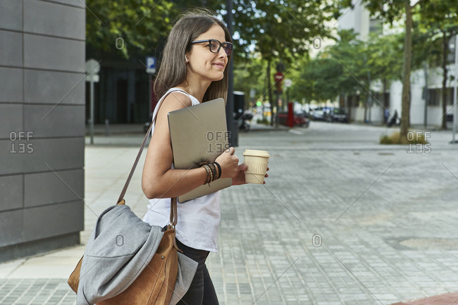 Thoughtful businesswoman holding laptop and disposable glass while walking on city street