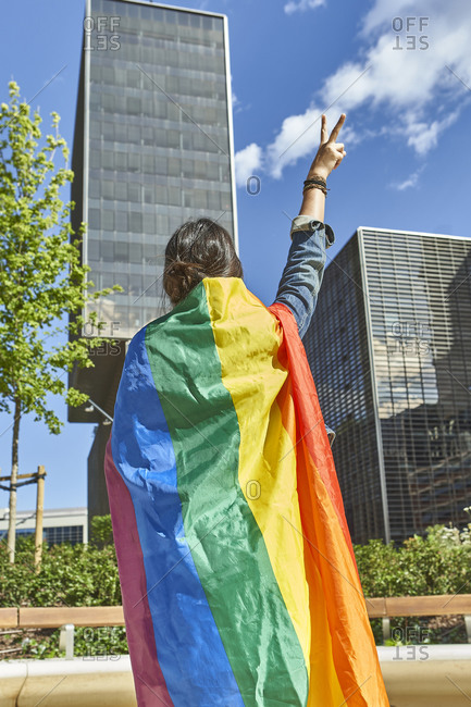 Woman gesturing peace sign while carrying rainbow flag in city