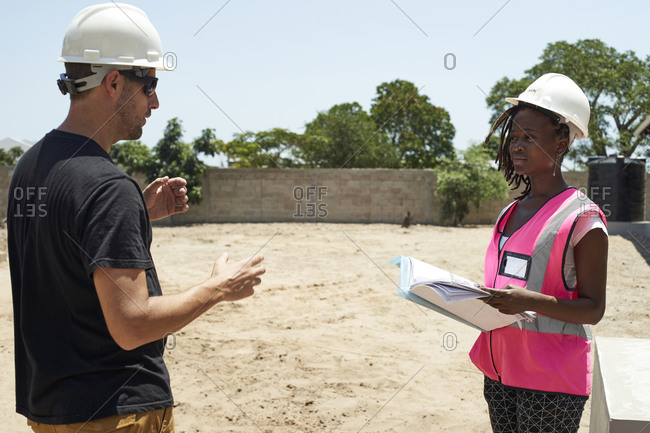 Coworkers wearing helmets discussing while standing at construction site during sunny day