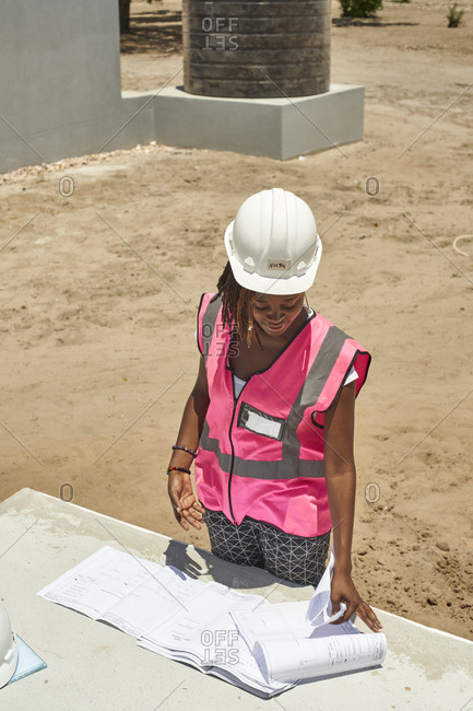 Female building contractor analyzing blueprint on table at construction site