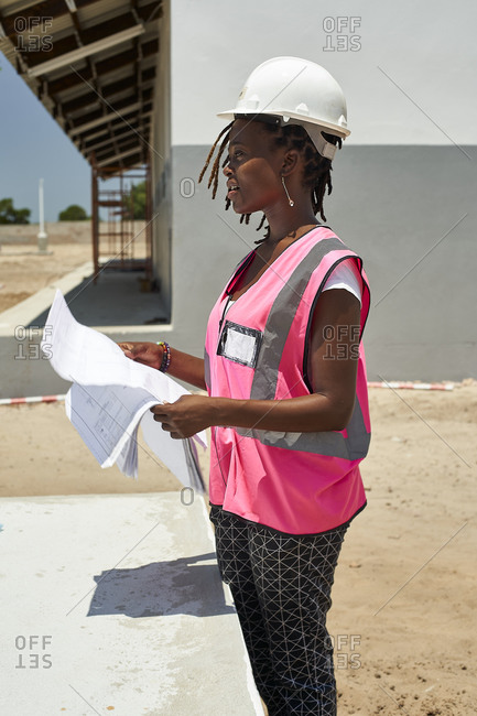 Female architect holding blueprint looking away while standing against school building at site