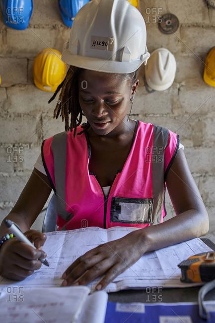 Female architect analyzing blueprint on desk while sitting in school