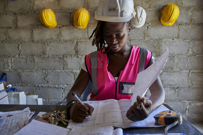 Female building contractor analyzing blueprint on desk while sitting in school