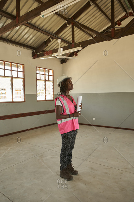 Female architect holding blueprint standing in school building at construction site