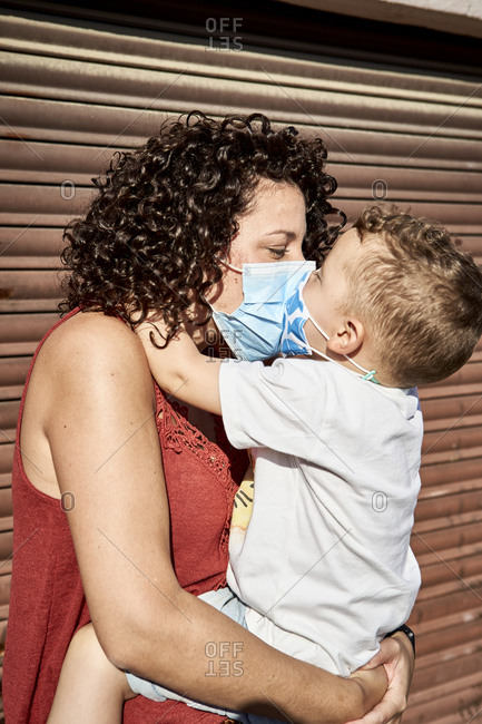 Mother carrying son with masks kissing him while standing against closed shutter