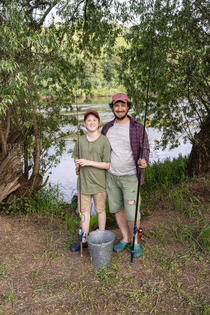 Happy father and son holding fishing rods while standing at riverbank