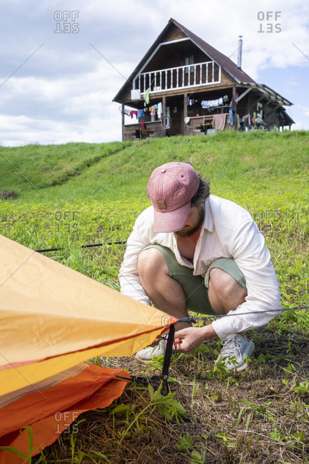 Mid adult man wearing cap installing tent on grassy land at campsite against sky