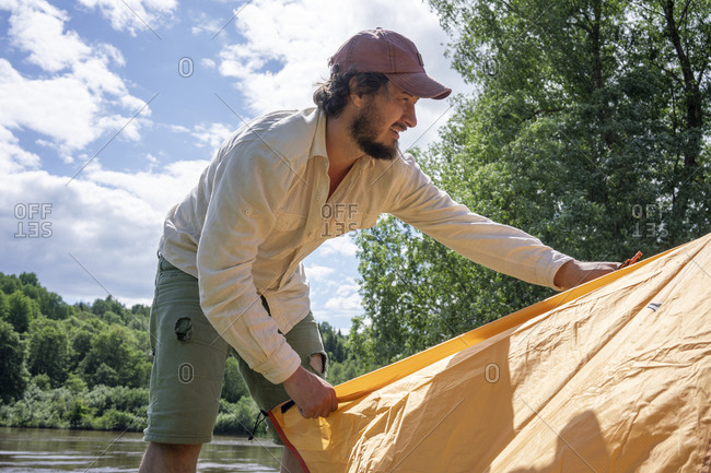 Mid adult man installing tent in forest against sky at campsite