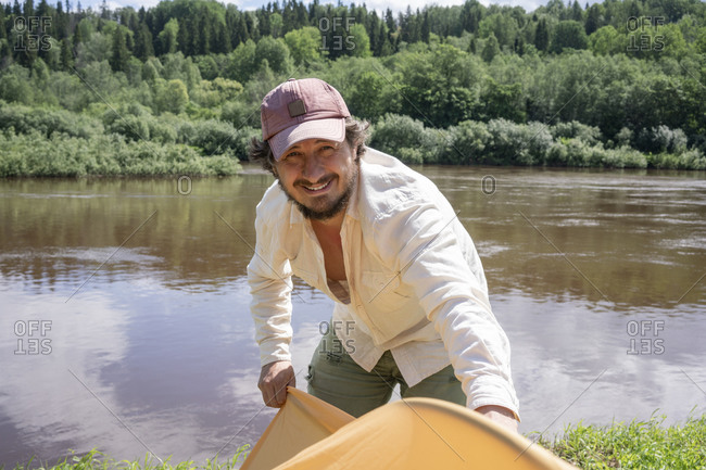 Smiling mid adult man installing tent while standing against lake in forest