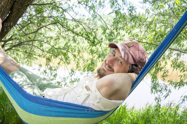 Smiling man relaxing on hammock at riverside