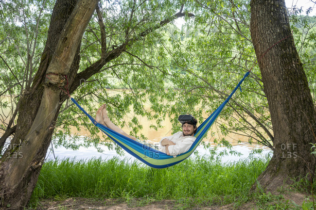 Man with 3d glasses relaxing on hammock at riverside