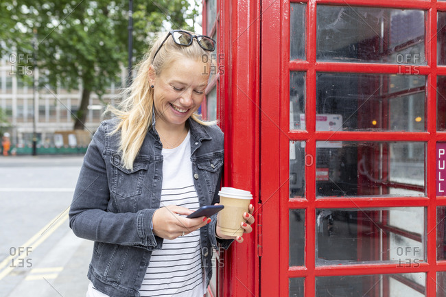 Smiling woman holding coffee cup using smart phone while standing by telephone booth
