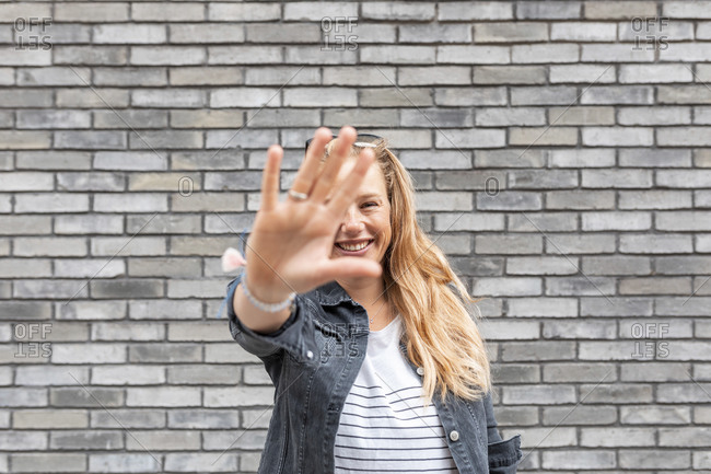 Smiling woman hiding face with hand while standing against gray brick wall