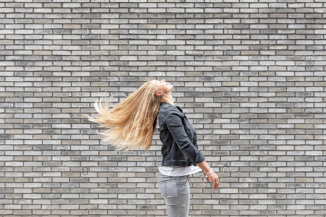 Woman tossing long hair while standing by gray brick wall