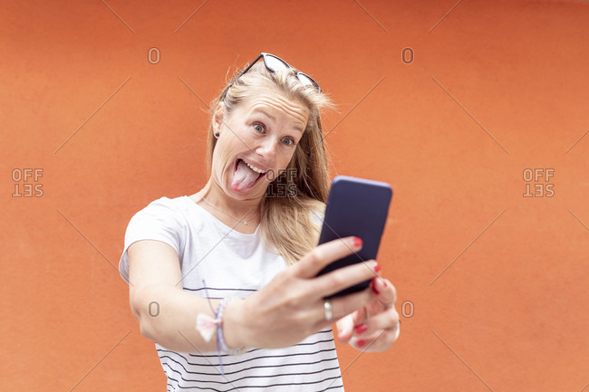 Playful woman sticking out tongue while taking selfie with smart phone against orange wall