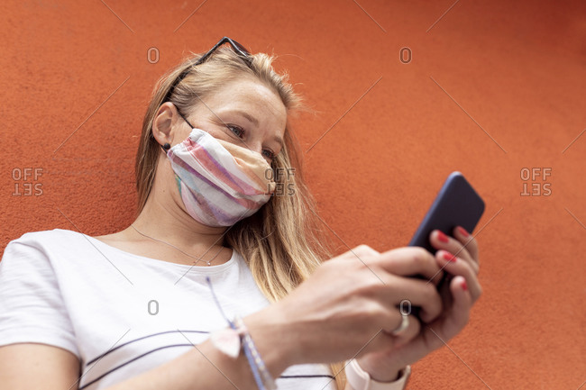 Woman wearing mask using smart phone while standing against orange wall
