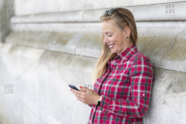 Smiling woman wearing checked shirt using mobile phone while leaning on wall