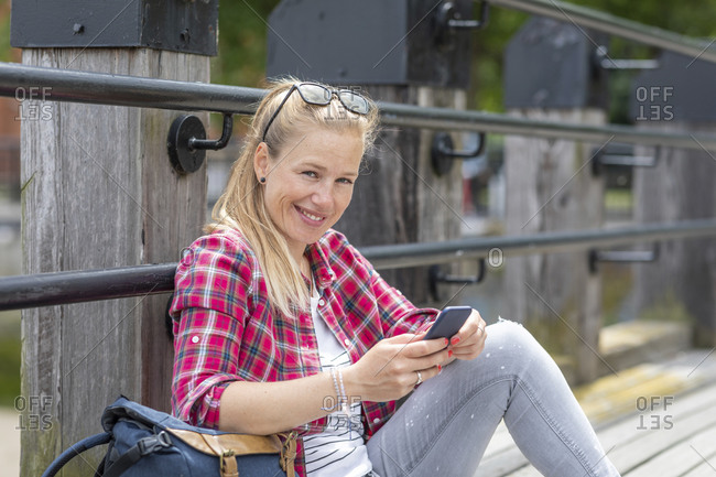 Smiling mid adult woman using smart phone while sitting by railing on pier
