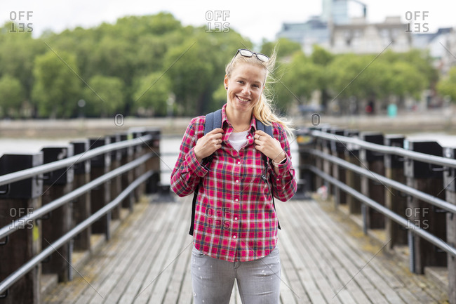 Smiling mid adult woman wearing checked shirt standing on bridge in city