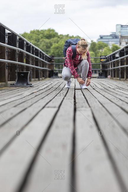 Mid adult woman tying shoelace while crouching on bridge in city