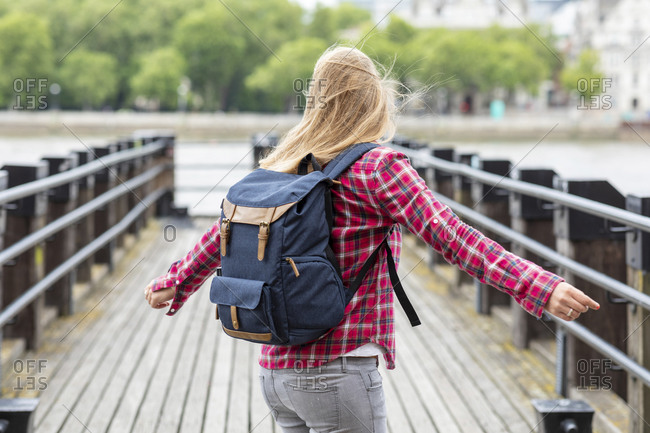 Happy woman wearing checked shirt with backpack spinning on bridge