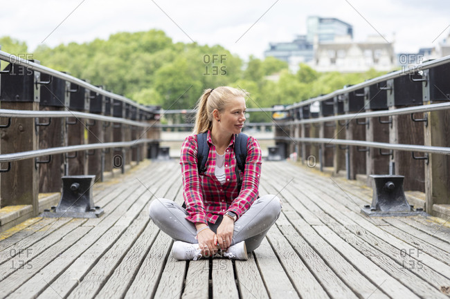 Mid adult woman wearing checked shirt looking away while sitting on bridge