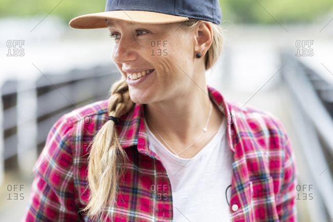 Close-up of mid adult woman with braided hairstyle wearing cap while looking away