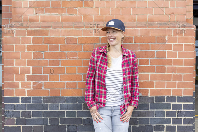 Smiling woman wearing checked shirt and cap while standing against brick wall