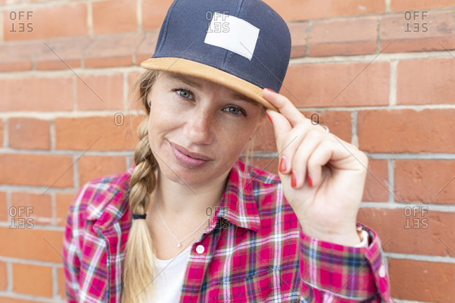Close-up of woman with braided hair wearing cap against brick wall