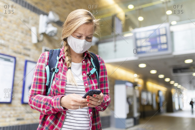 Woman wearing mask using smart phone while standing at tube station