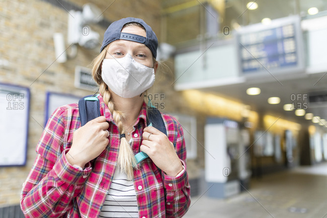 Close-up of woman with braided hair wearing mask and cap while standing at tube station