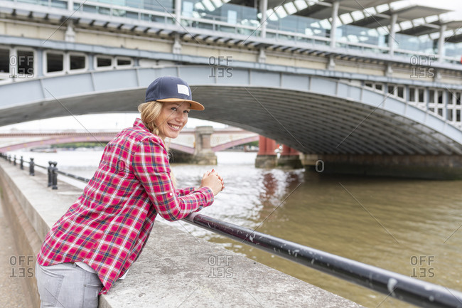 Smiling woman wearing checked shirt and cap while standing by railing against bridge