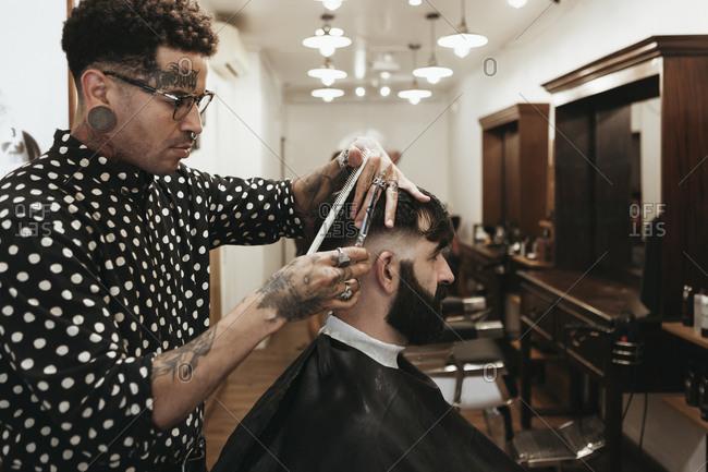Fashionable hairdresser styling man's hair at salon