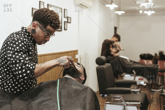 Trendy barber styling client's beard at salon